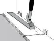 Montuojant paskutinę grindlentę eilėje, naudokite laužtuvėlį ir plaktuką kad lenta tiksliai įsistatytų į reikiamą vietą.